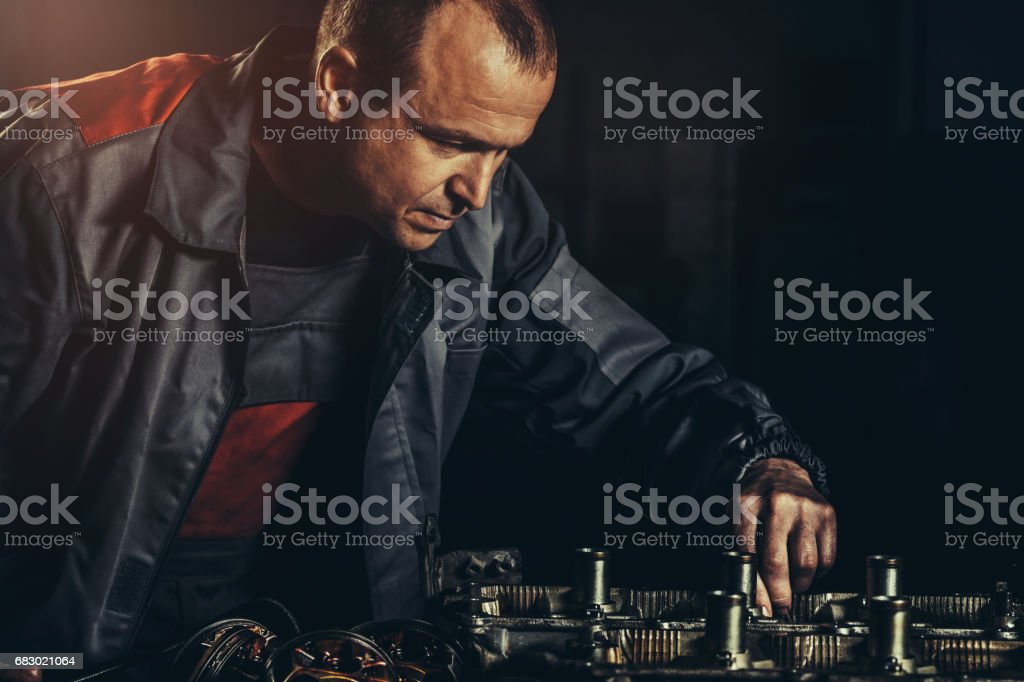 Professional car mechanic repairing V8 engine in auto repair shop stock photo