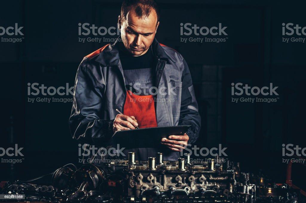 Professional car mechanic repairing V8 engine in auto repair shop stock photo