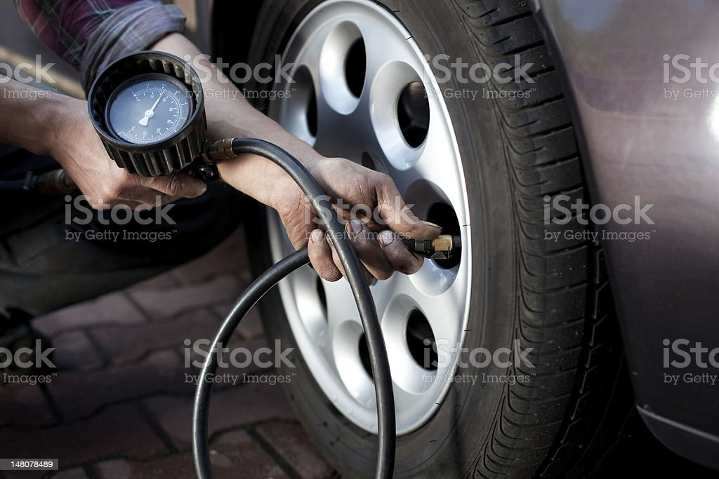 Professional checking and adjusting tire pressure stock photo
