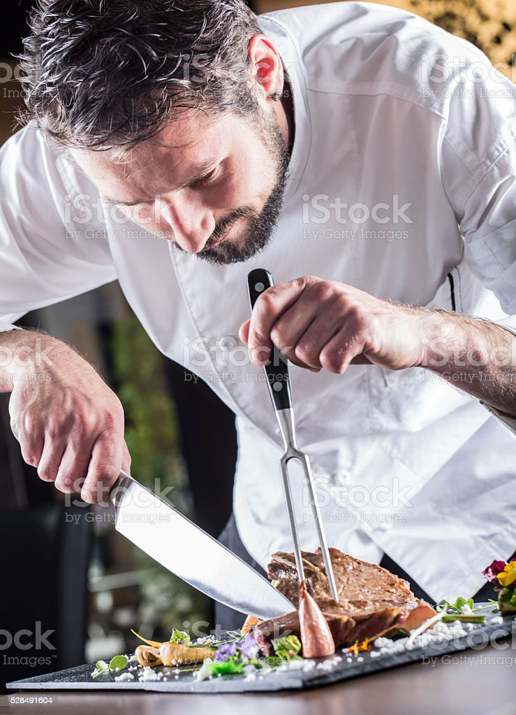 Professional chef in a restaurant prepares or cut up t-bone stock photo