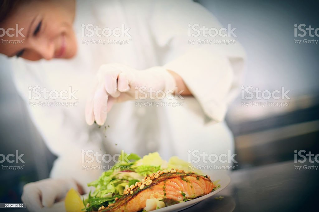 Professional chef places finishing touches on meal stock photo