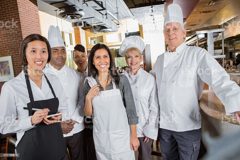 Professional chefs and waitstaff meeting with manager in restaurant kitchen royalty-free stock photo