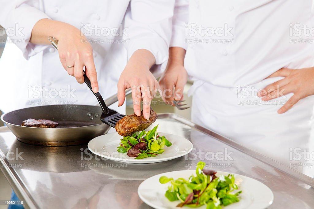 Professional chefs prepares steak dishes at restaurant stock photo