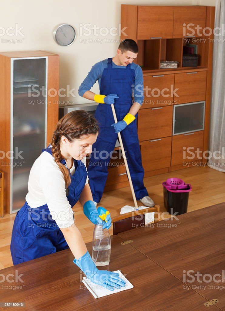 Professional cleaners cleaning in room stock photo