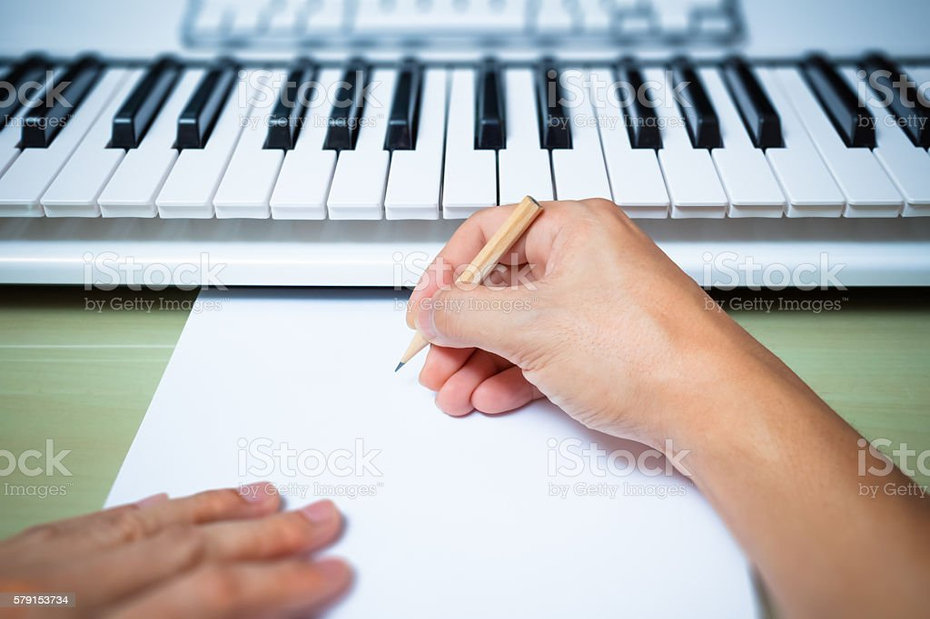 professional composer hands writing songs on blank white paper stock photo