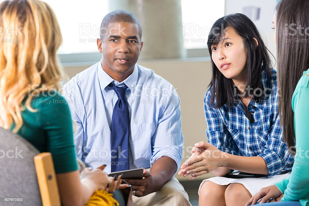Professional counselor talks with patient in group therapy stock photo