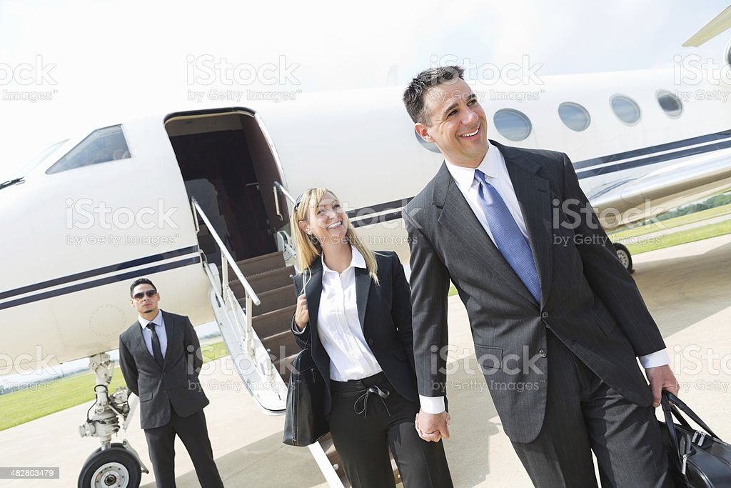 Professional couple exiting corporate jet; business travel stock photo