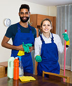professional couple in uniform cleaning at domestic interior