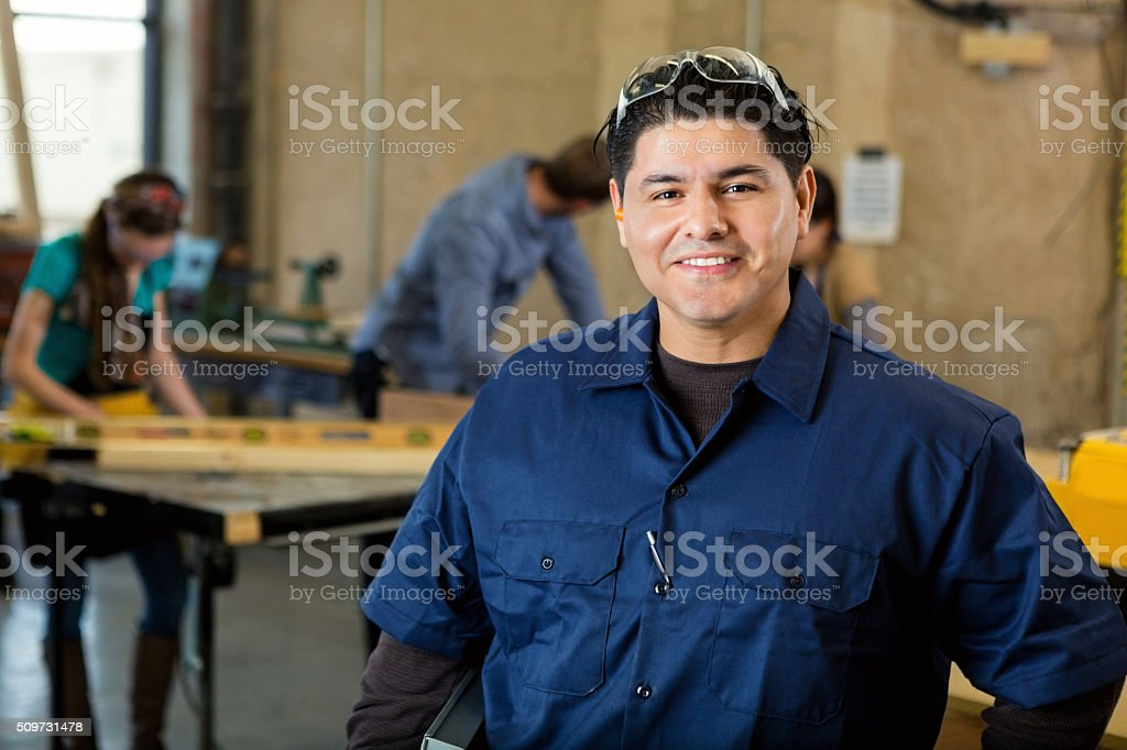 Professional craftsman in large workshop with heavy machinery and tools stock photo