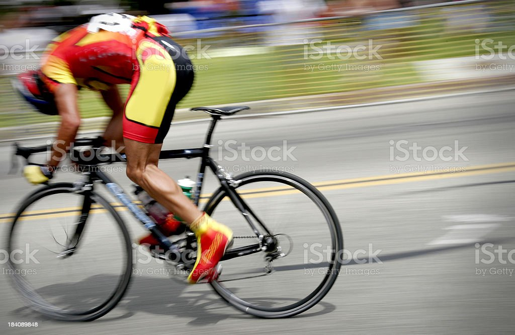Professional cyclist races on road with head down royalty-free stock photo