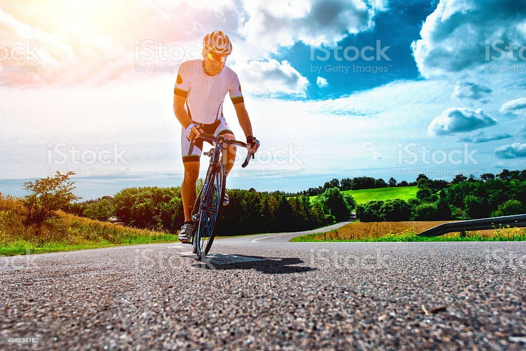 Professional cyclist rides bike with power up a hill stock photo