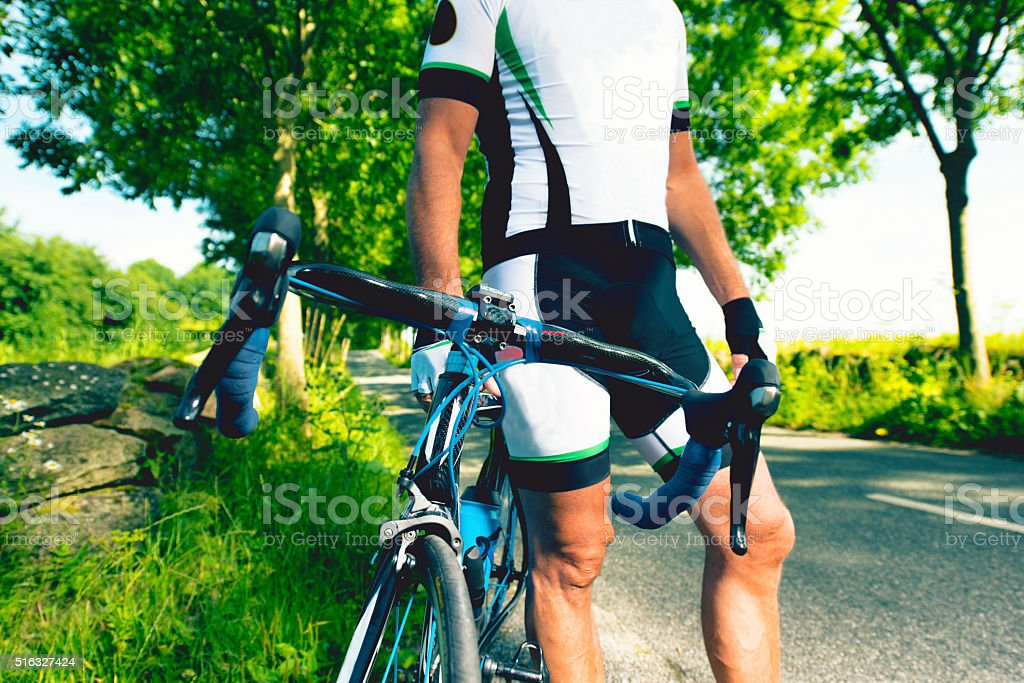 Professional cyclist stands next to his bicycle at road stock photo