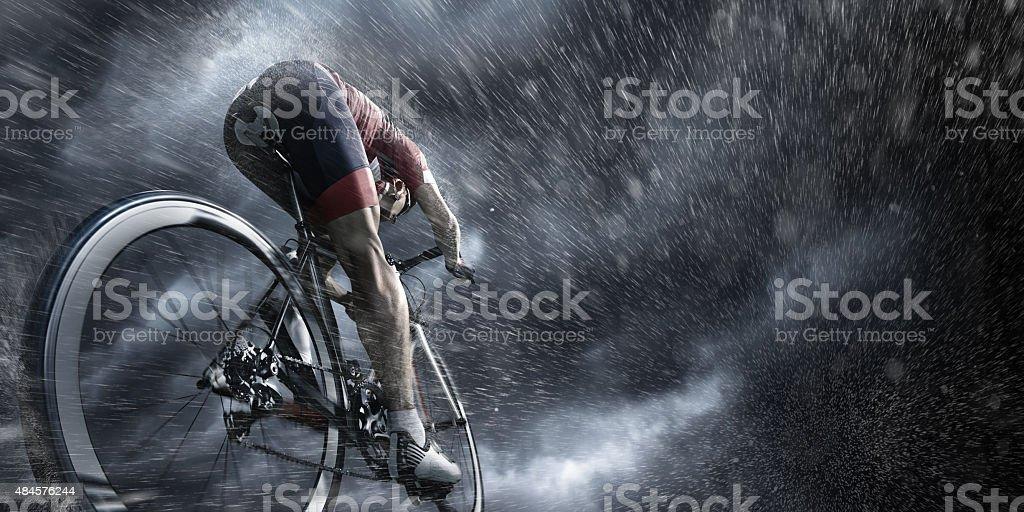 Professional cyclist under stormy sky stock photo
