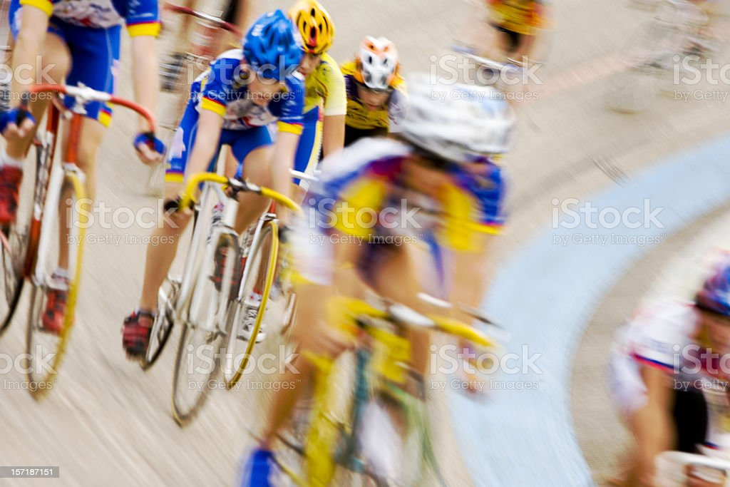 Professional cyclists racing in peloton formation around a velodrome stock photo
