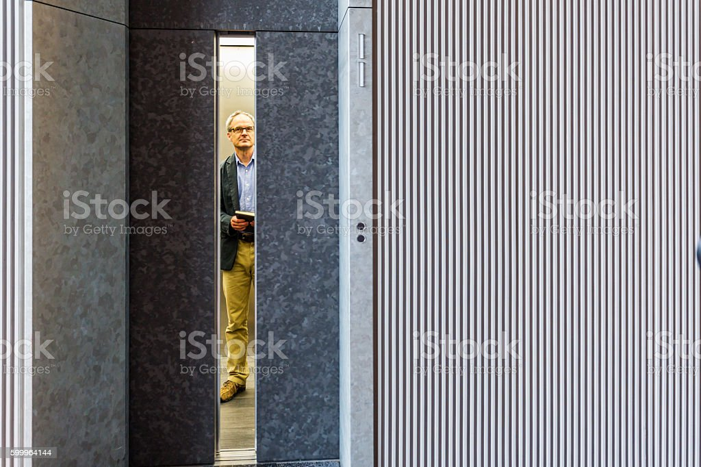 Professional English Businessman Waiting for Modern Corporate Office Building Elevator stock photo