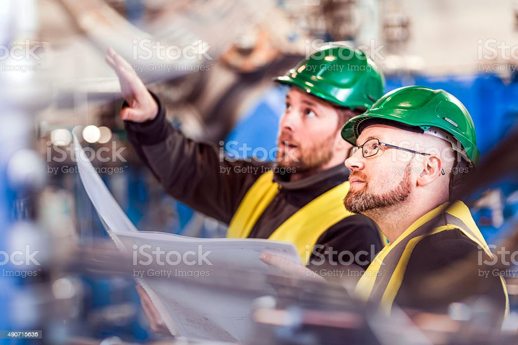 Professional explaining colleague while analyzing machinery in f stock photo