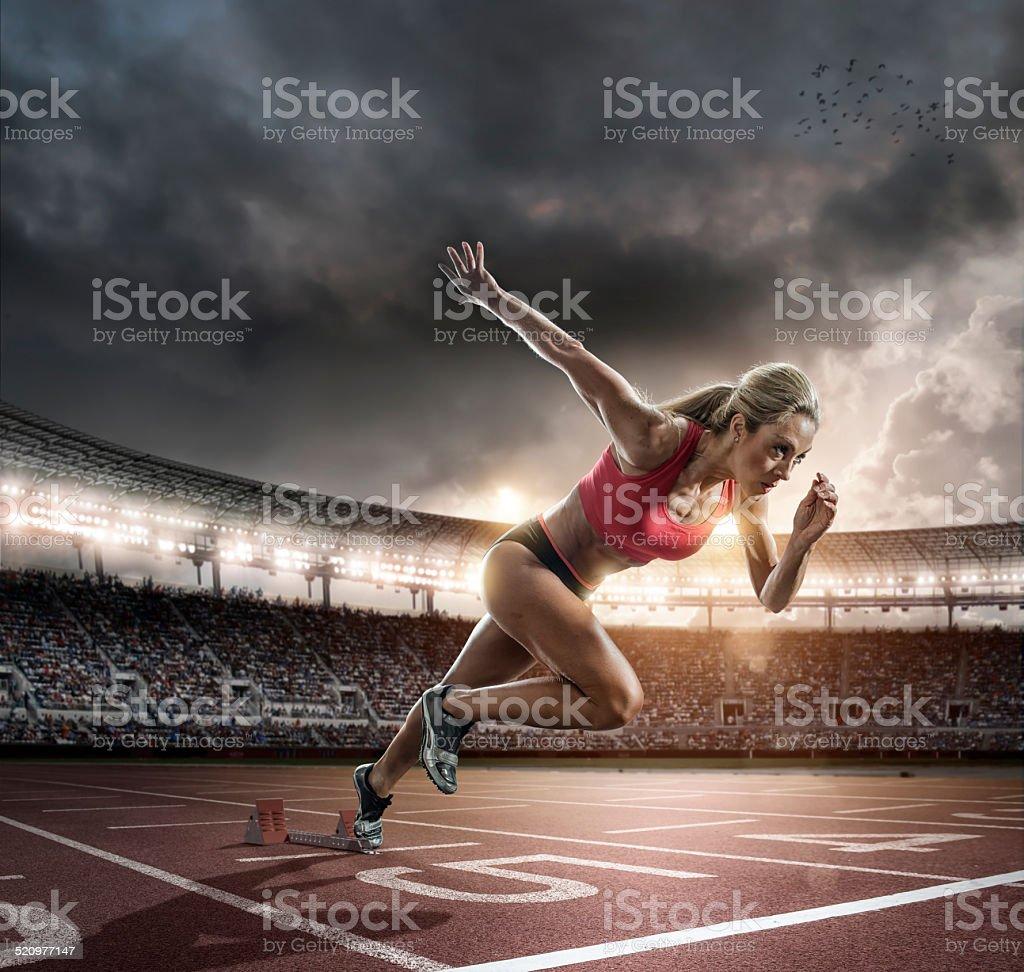 Professional Female Athlete Sprinting Off Blocks stock photo