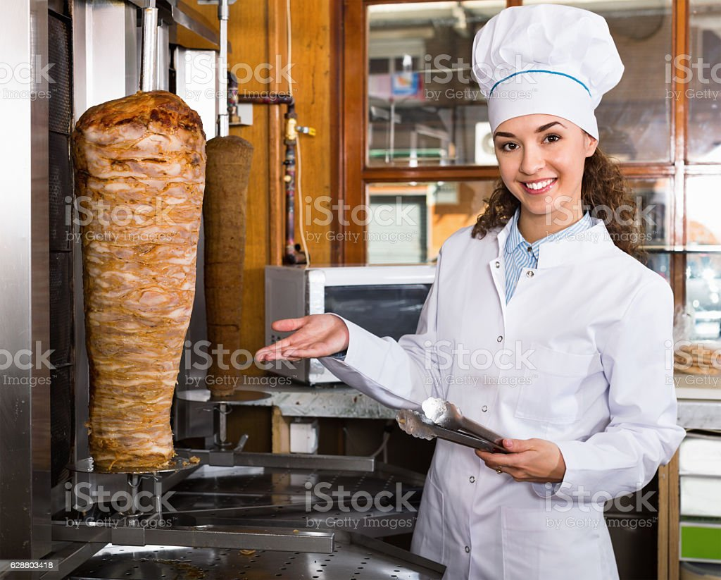 Professional female cook with grilled meat on spit for kebab stock photo