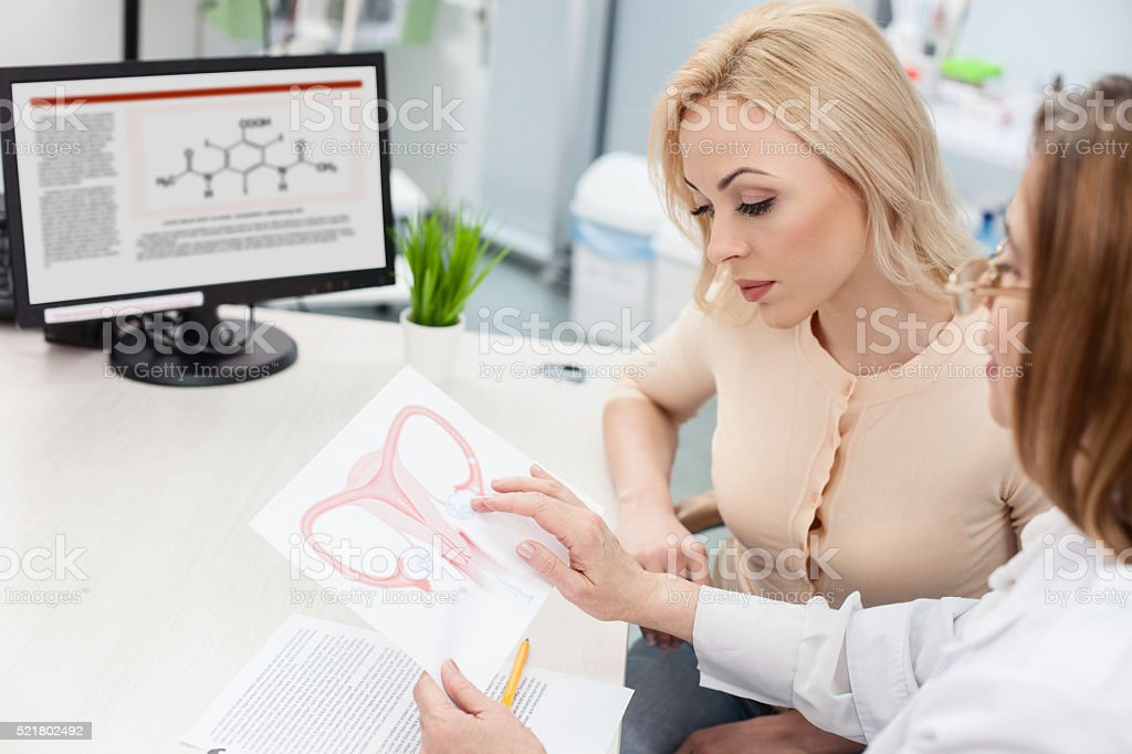 Professional female doctor is consulting blond lady stock photo