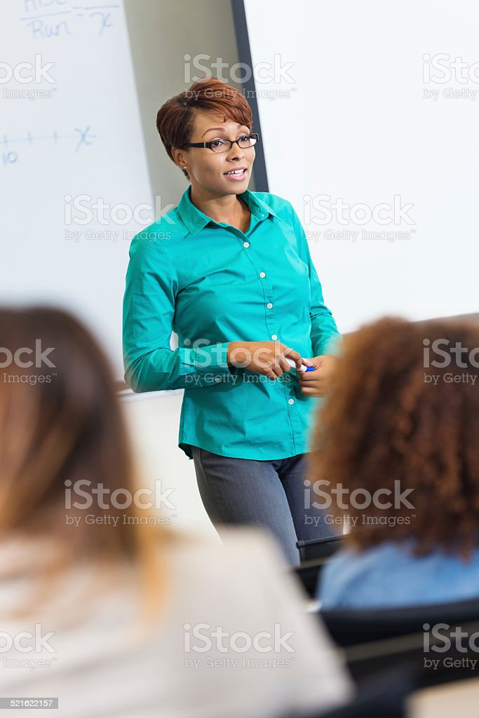 Professional female teacher speaking to clsassroom of students stock photo