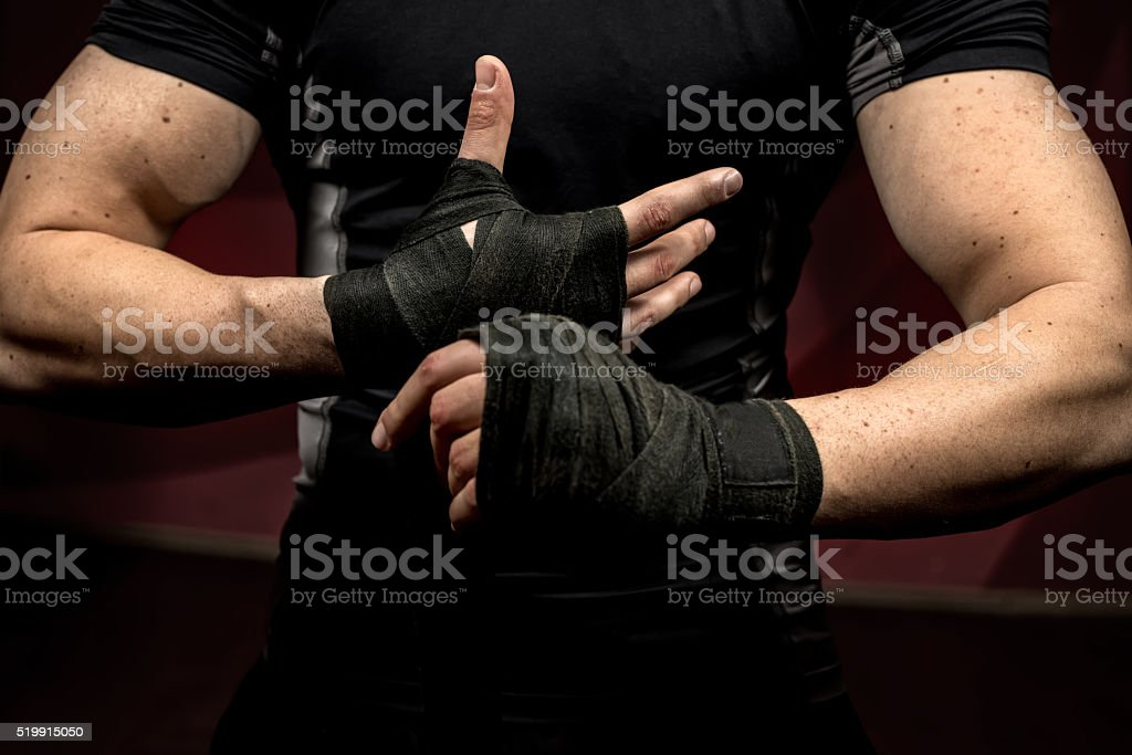 professional fighter preparing for training, wraping his hands and wrists stock photo