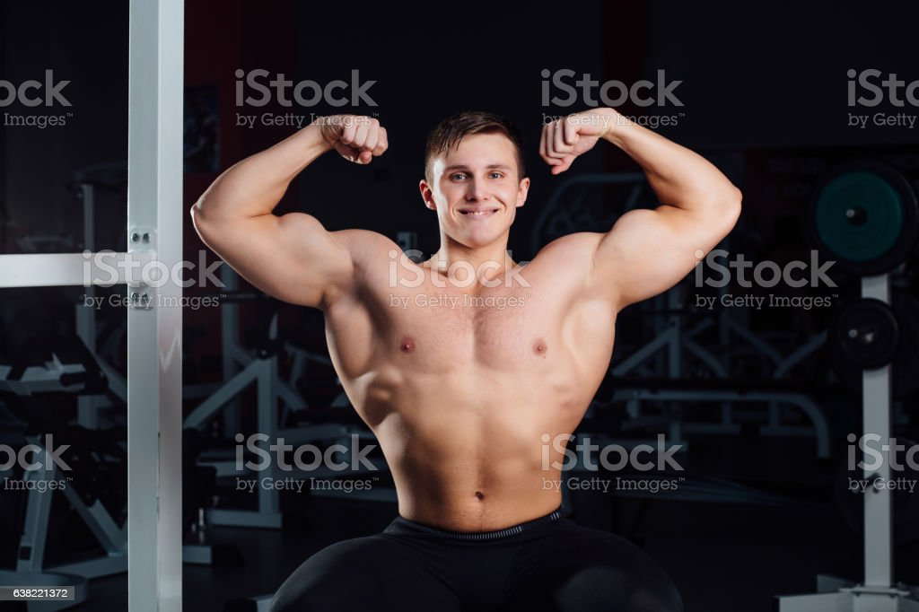 professional fitness bodybuilder sitting on the bench and demonstrates muscles stock photo