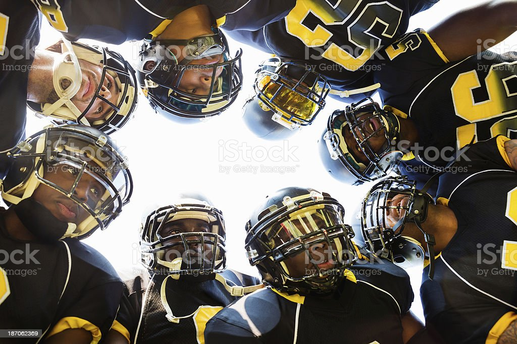 Professional football players huddled while in time out during game stock photo