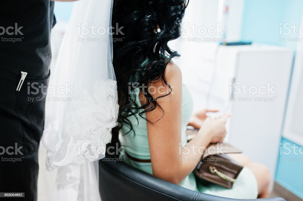Professional hairdresser puts a veil on the head of  beautiful brunette model at salon of beauty stock photo