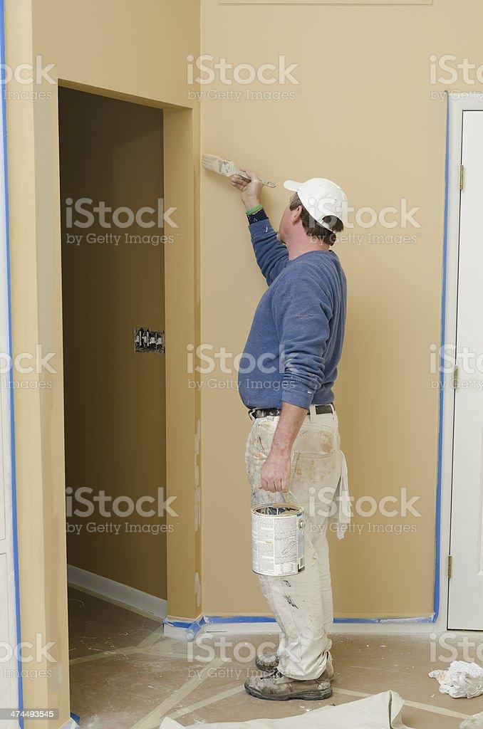 Professional house painter brushing a corner stock photo