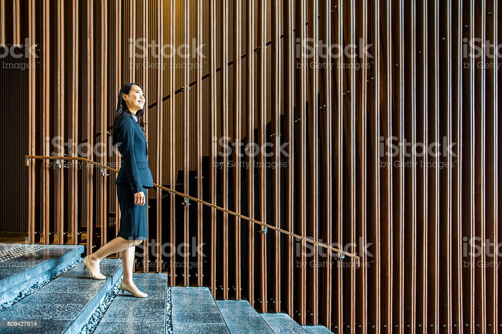 Professional Japanese Businesswoman Walking on Stairs in an Office Lobby stock photo