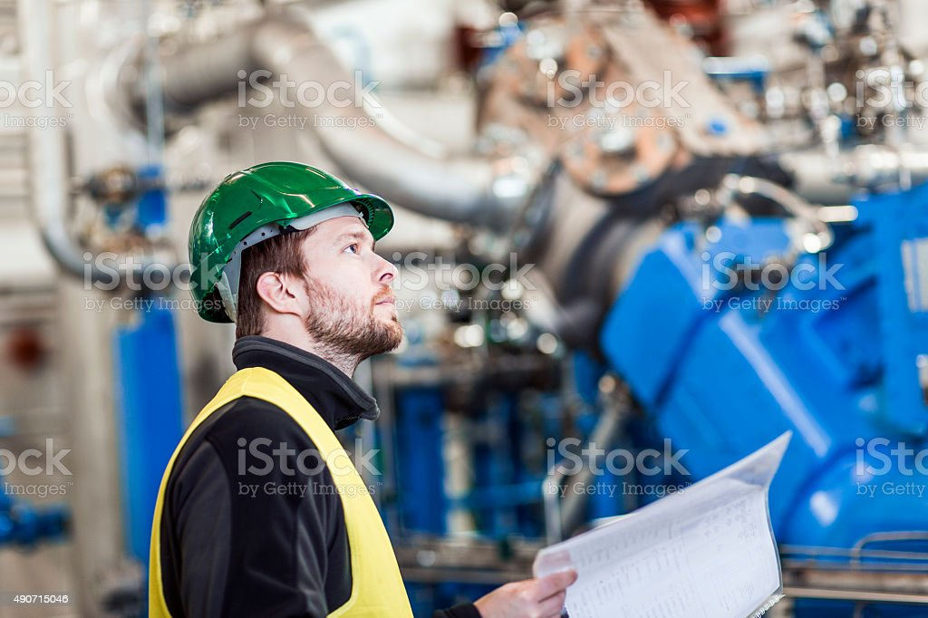 Professional looking at machines while holding document in offic stock photo