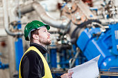 Professional looking at machines while holding document in offic