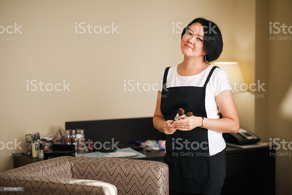 Professional makeup artist with brushes in hand, attractive asian woman stock photo