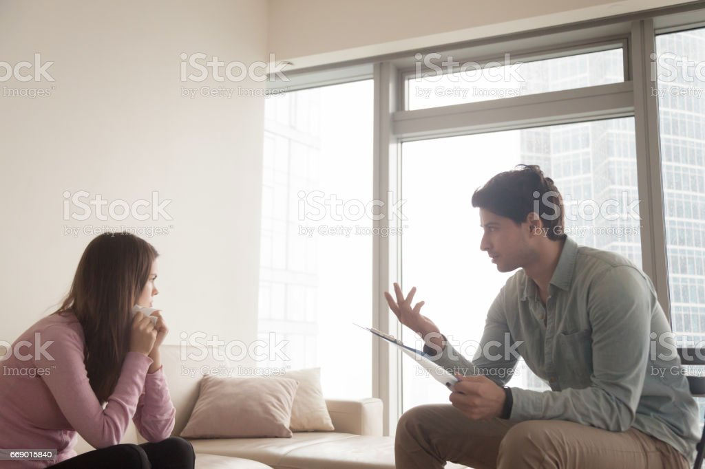 Professional male psychologist talking to upset crying woman, psychotherapy session stock photo