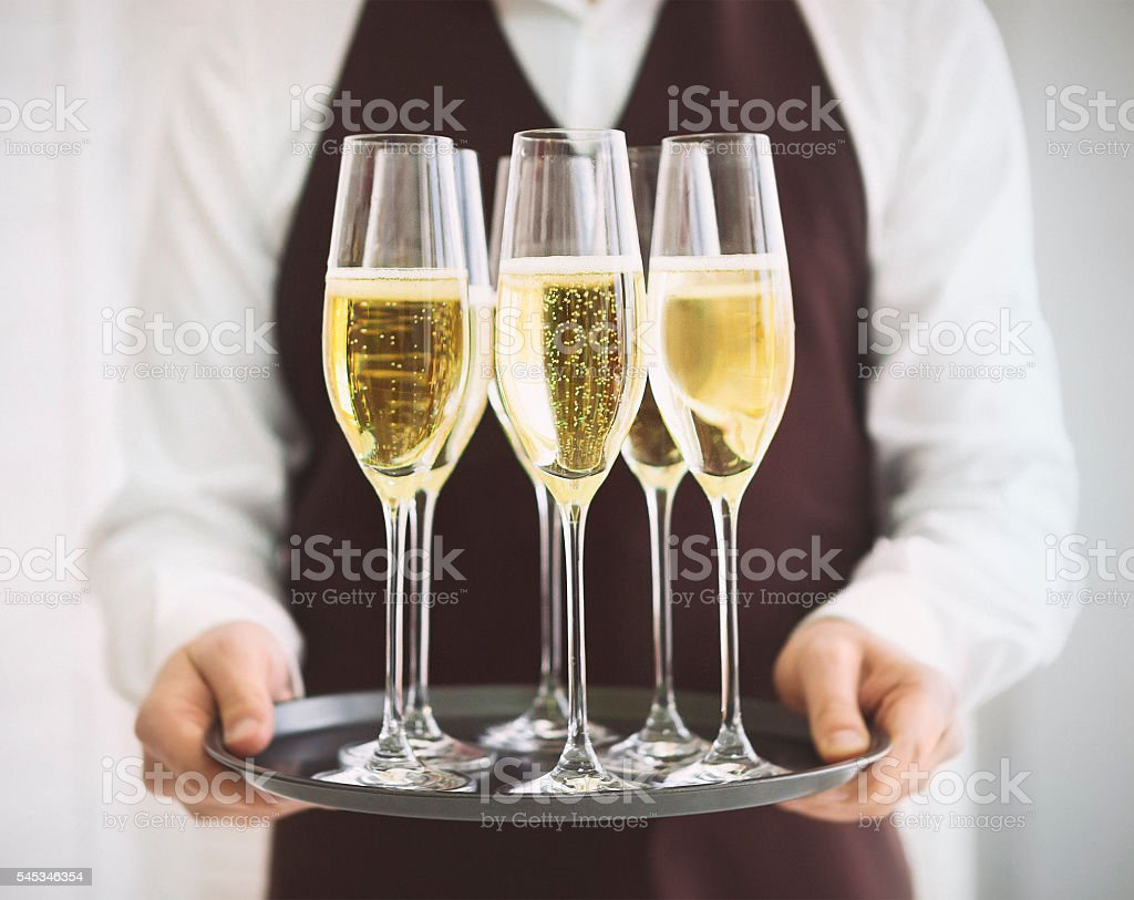 Professional male waiter in uniform serving champagne. DOF. stock photo