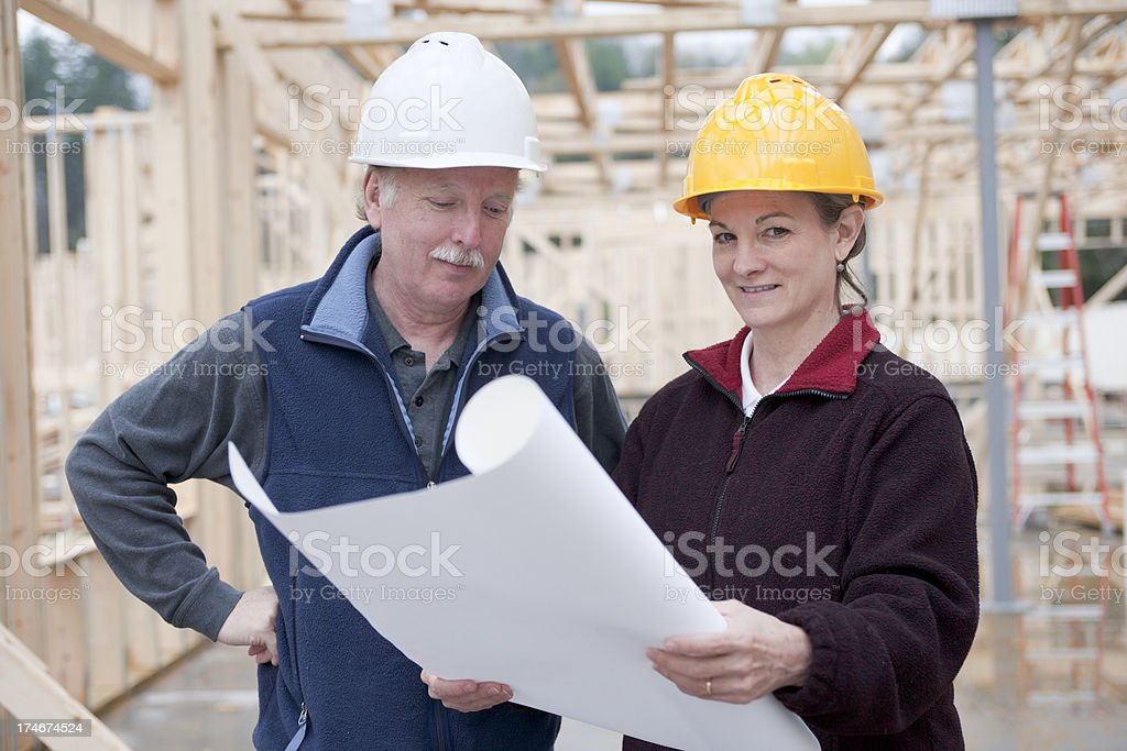 Professional man and woman at construction site royalty-free stock photo