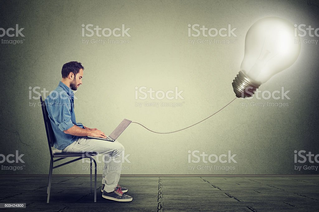 professional man using laptop with light bulb plugged stock photo