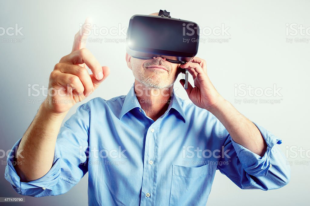 Professional Man Using Virtual Reality Headset And Mobile Phone stock photo