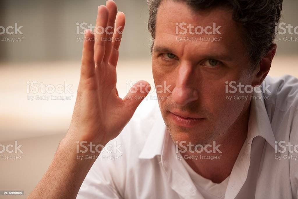 Professional man with raised hand in forceful gesture stock photo