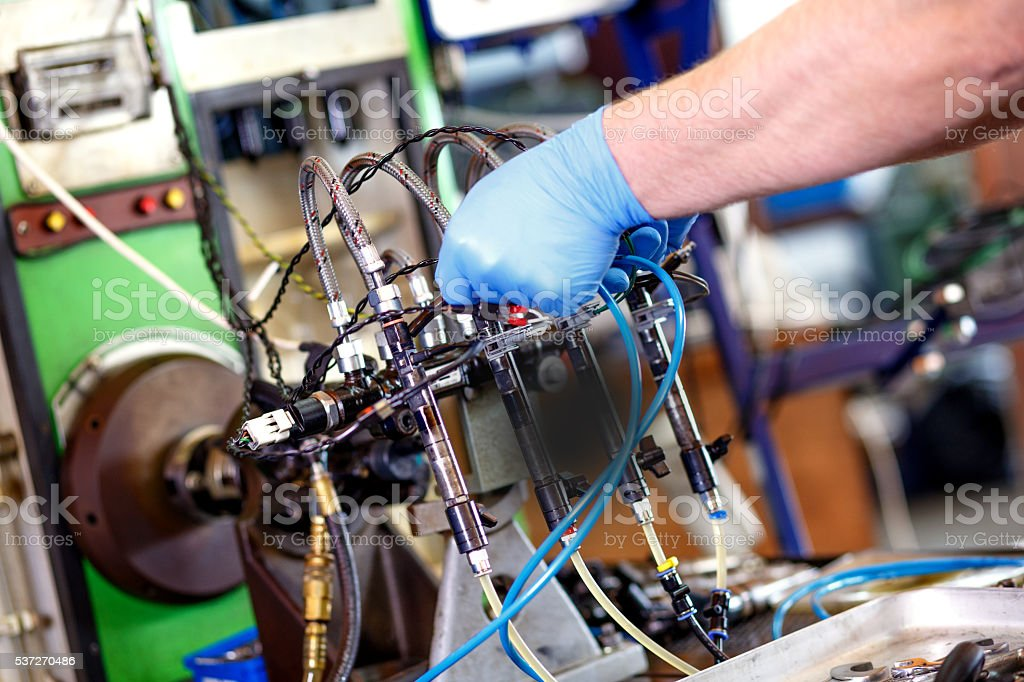 Professional mechanic testing diesel injector stock photo