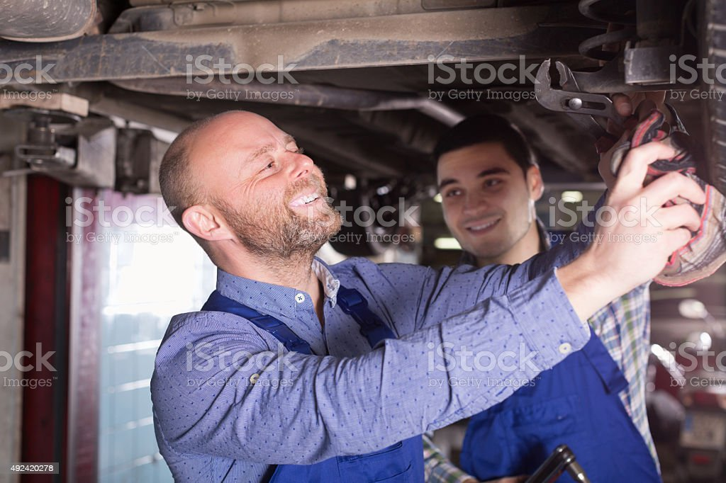 Professional mechanics repairing car stock photo