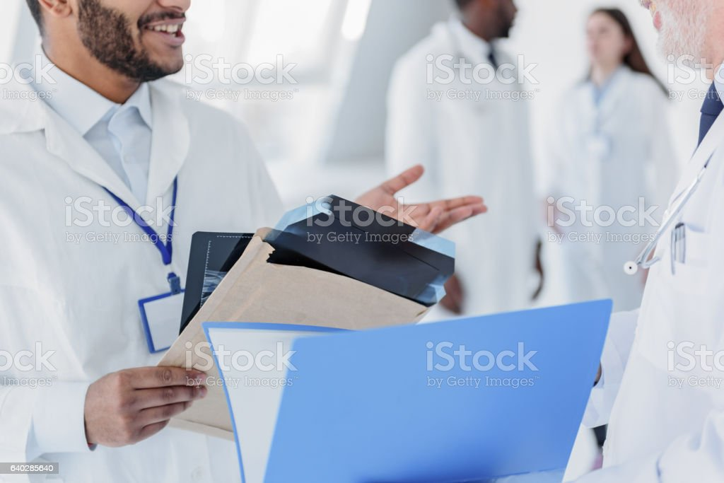 Professional medical team discussing radiograph stock photo