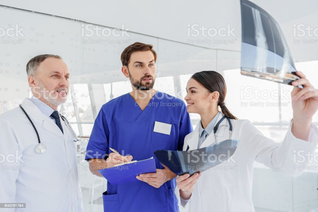 Professional medical team discussing roentgen picture stock photo
