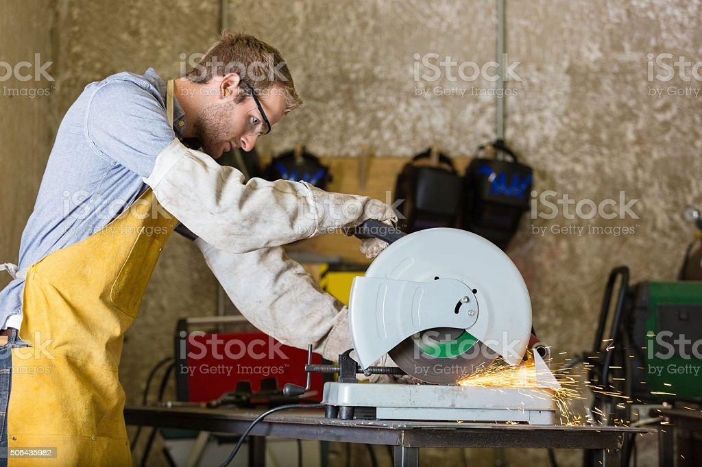 Professional metalworker using metal saw in workshop or studio stock photo