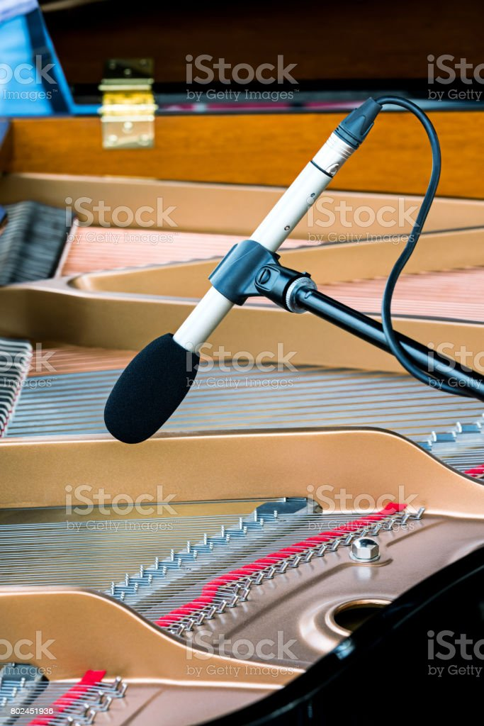 professional microphone standing above strings of grand piano stock photo