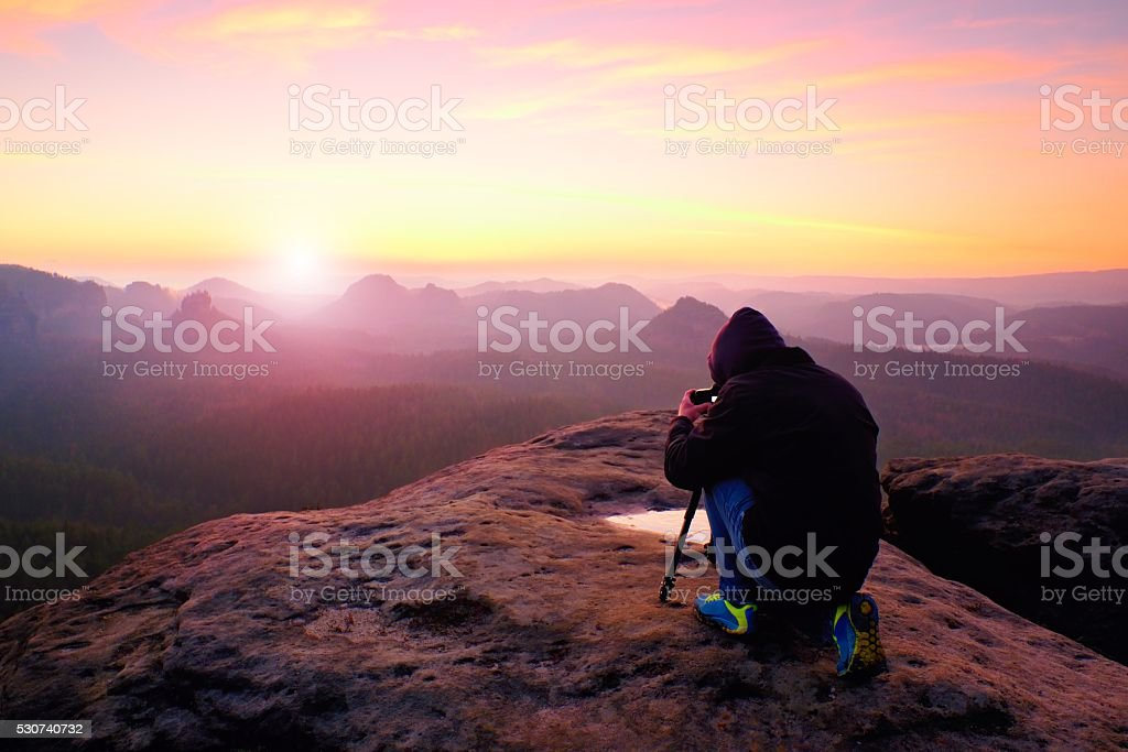 Professional nature photographer takes photos with mirror camera on rock. stock photo