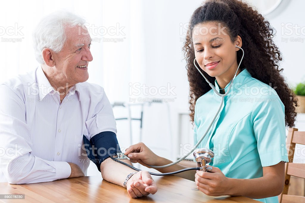 Professional nurse checking patient's blood pressure stock photo