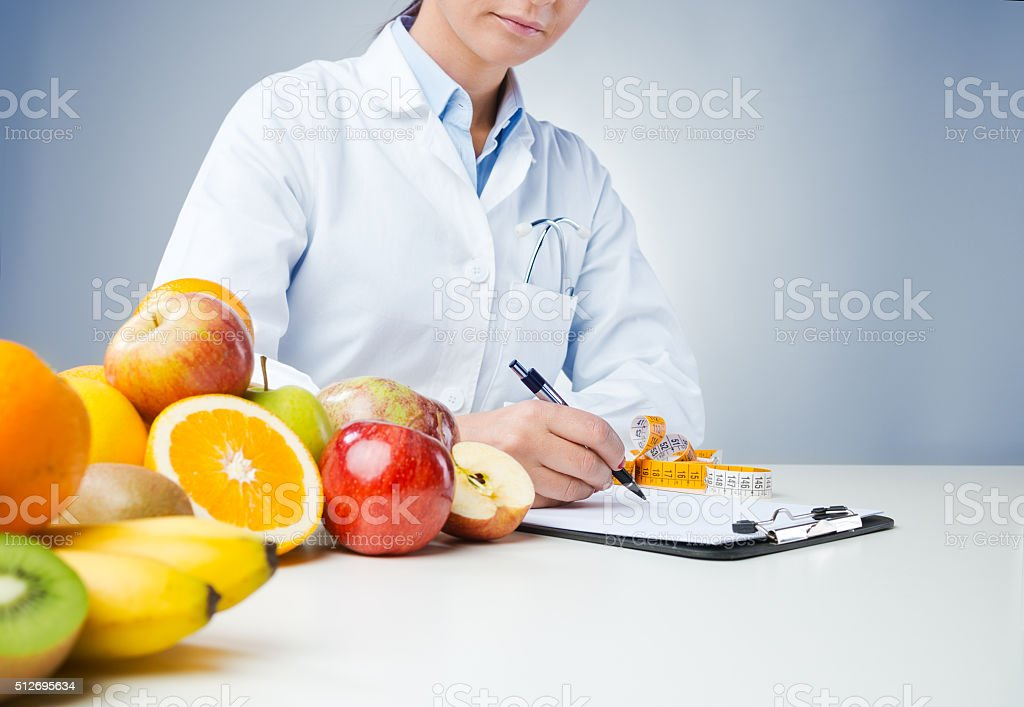 Professional nutritionist writing medical records stock photo