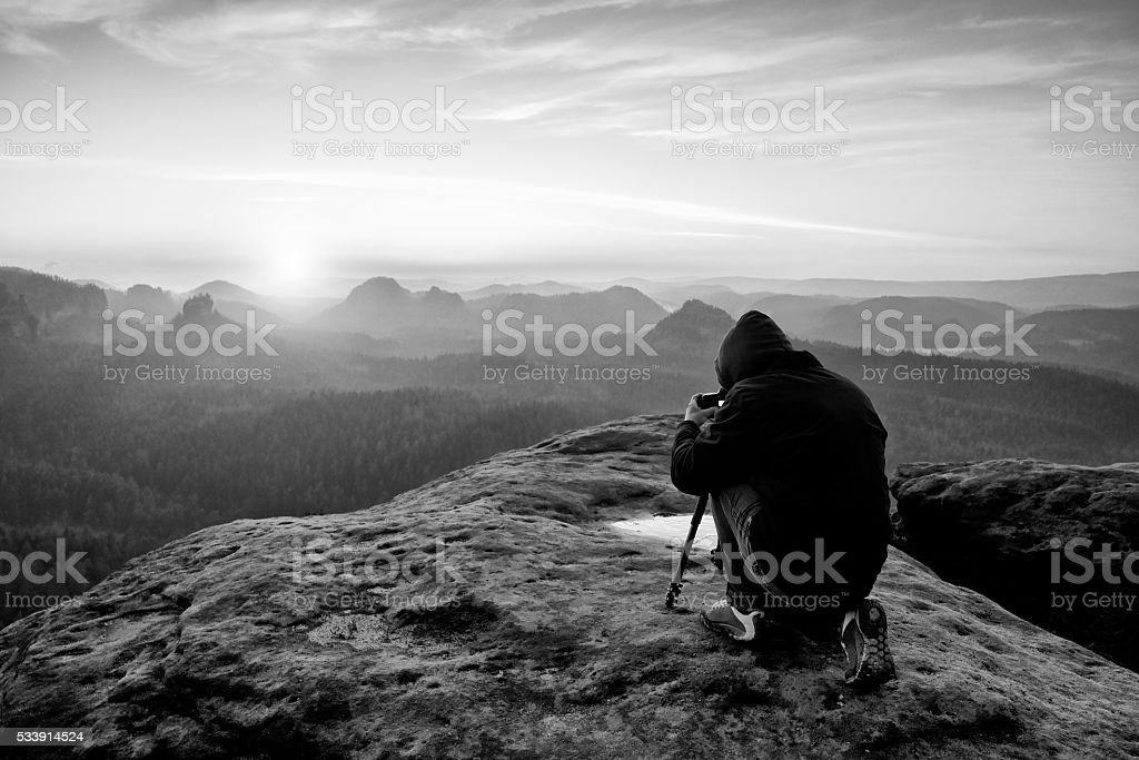 Professional on cliff. Nature photographer takes photos with camera stock photo