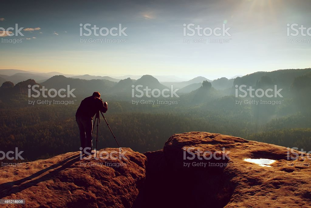Professional on cliff. Nature photographer takes photos with mirror camera stock photo